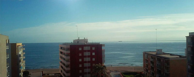 En el horizonte, un barco mercante se dirige hacia el Puerto de Valencia, navegando sobre un mar apenas rizado.