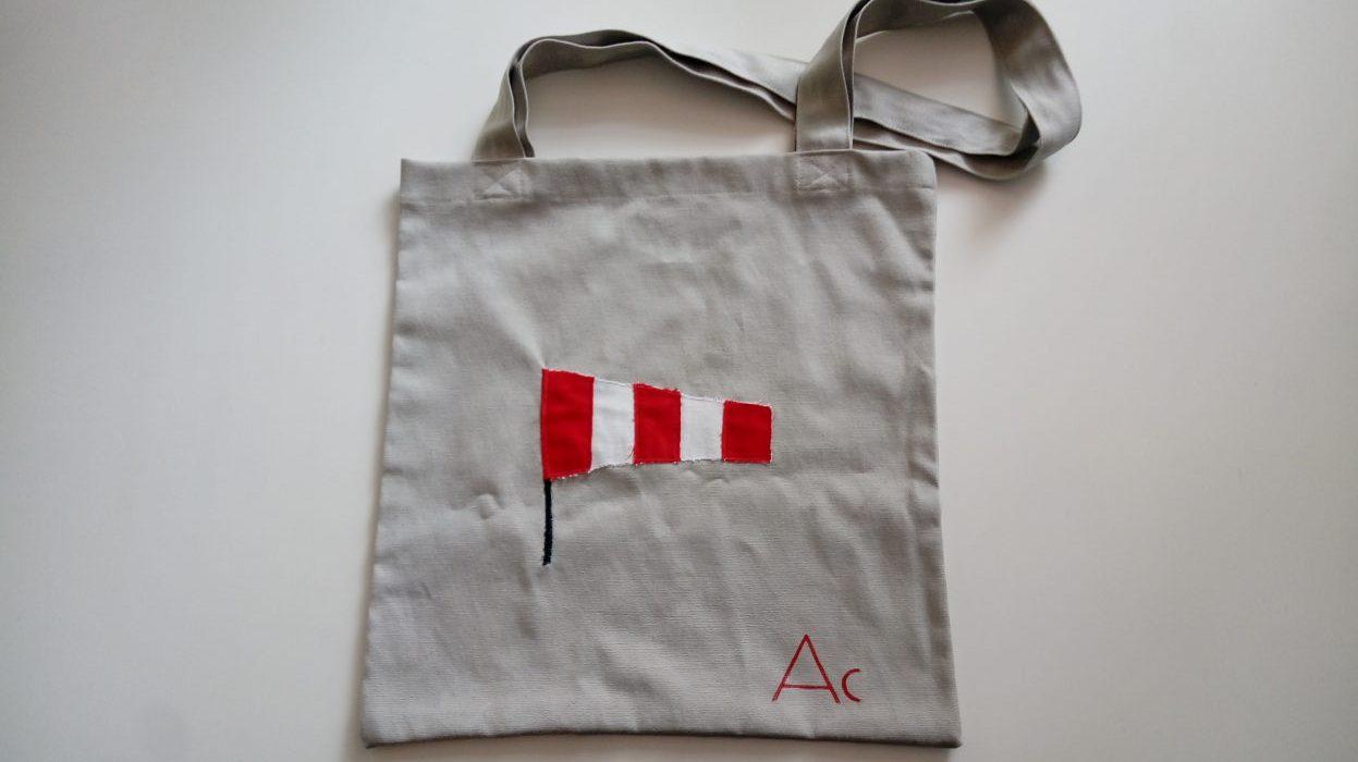 Bolsa de tela con una manga de viento roja y blanca.
